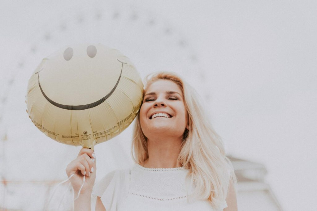 Ragazza sorridente con palloncino smile