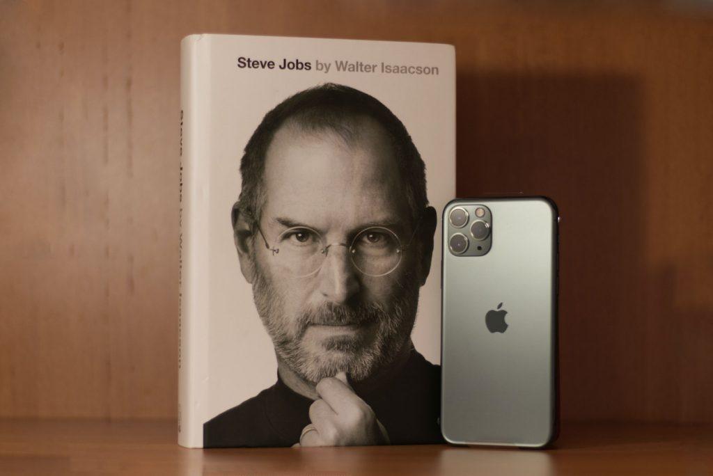 Primo piano di Steve Jobs su libro accanto ad iPhone